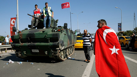 A man wrapped in a Turkish flag walks past a military vehicle in front of Sabiha Airport, in Istanbul, Turkey July 16, 2016 © Baz Ratner