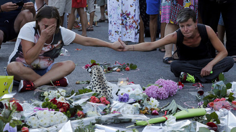 People react near flowers placed on the road in tribute to victims, two days after an attack by the driver of a heavy truck who ran into a crowd on Bastille Day killing scores and injuring as many on the Promenade des Anglais, in Nice, France, July 16, 2016. © Pascal Rossignol