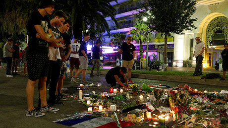 People react near flowers placed on the road in tribute to victims, three days after an attack by the driver of a heavy truck who ran into a crowd on Bastille Day killing scores and injuring as many on the Promenade des Anglais, in Nice, France, July 17, 2016 © Pascal Rossignol