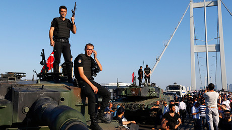 Policemen stand atop military armored vehicles after troops involved in the coup surrendered on the Bosphorus Bridge in Istanbul, Turkey July 16, 2016 © Murad Sezer
