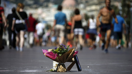 People walk near a bouquet of flowers placed in tribute to victims of the truck attack along the Promenade des Anglais on Bastille Day killing scores and injuring as many in Nice, France, July 17, 2016. © Eric Gaillard