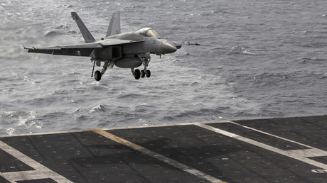 A US Navy F/A-18 aircraft prepares to land on the runway of the US Navy aircraft carrier USS George Washington, during a tour of the ship in the South China Sea © Tyrone Siu