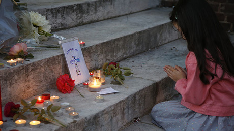 A young girl prays near flowers and candles at the town hall in Saint-Etienne-du-Rouvray, France, to pay tribute to French priest who was killed with a knife and another hostage seriously wounded in an attack on a church that was carried out by assailants linked to Islamic State. © Pascal Rossignol