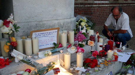 A man kneels near flowers and candles at the town hall in Saint-Etienne-du-Rouvray, near Rouen in Normandy, France, to pay tribute to French priest, Father Jacques Hamel, who was killed with a knife in an attack on a church © Pascal Rossignol