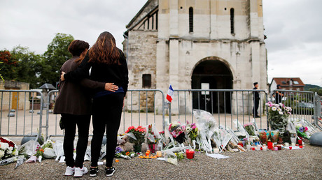 People stand in front of a make shift memorial in front of the Saint-Etienne du Rouvray church on July 27, 2016, after the priest Jacques Hamel was killed on July 26 in his church during a hostage-taking claimed by Islamic State group. © AFP