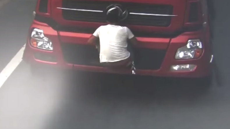 License to thrill: Chinese truck driver uses body to block registration plate