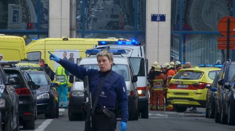 A police woman gestures in front of ambulances at the scene of a blast outside a metro station in Brussels, in this still image taken from video on March 22, 2016. ©