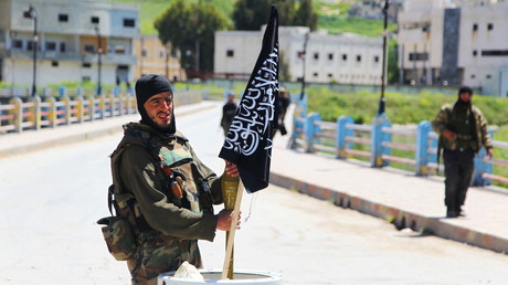 File photo: A Nusra Front fighter carries a shell near a Nusra Front flag on his weapon in Jisr al-Shughour town, after rebels took control of the areaю. © Ammar Abdullah