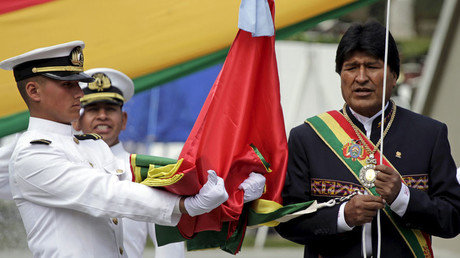 FILE PHOTO. Bolivia's President Evo Morales (R) flies the national flag during a ceremony as part of events commemorating the