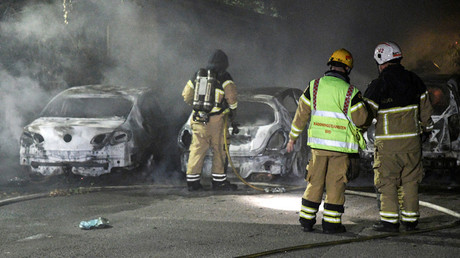 Firefighters extinguish a fire which had damaged cars after the vehicles had been set alight, in Malmo, Sweden, August 15, 2016. © Johan Nilsson