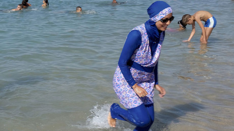 A woman wearing a burkini walks in the water on a beach in Marseille, France. © Stringer