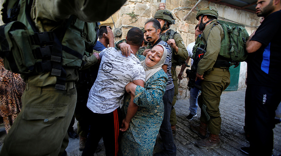 Israeli troops photographed beating unarmed Palestinian during 'routine check'