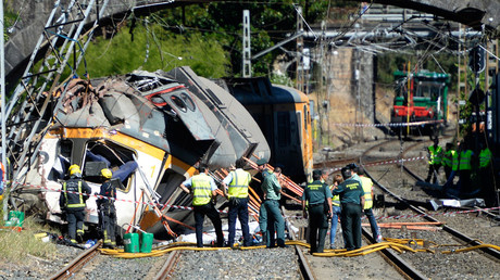 Spanish Guardia Civil policemen, firefighters and security members stand past the wreckage of a train derailed in O Porrino, northwestern Spain © Miguel Riopa