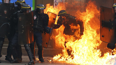 A French riot police officer is surrounded by flames, during a demonstration against the controversial labour reforms of the French government in Paris on September 15, 2016© Thomas Samson