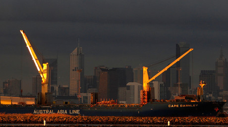 Cranes of a ship are seen in front of the skyline of Melbourne. © Mick Tsikas