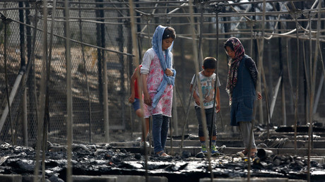 Migrants stand among the remains of a burned tent at the Moria migrant camp, after a fire that ripped through tents and destroyed containers during violence among residents, on the island of Lesbos, Greece, September 20, 2016. © Giorgos Moutafis