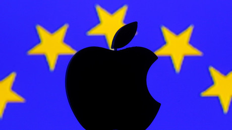 A 3D printed Apple logo is seen in front of a displayed European Union flag. © Dado Ruvic