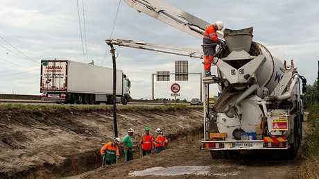 Workers pour concrete to build a wall near Calais migrant 'Jungle' camp along the road leading to the harbour of Calais, northern France on September 20, 2016 to stop migrants from jumping on lorries heading to Britain. © Philippe Huguen