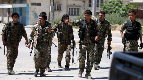 Kurdish fighters from the People's Protection Units (YPG) walk along a street in the southeast of Qamishli city, Syria © Rodi Said