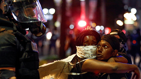 Two women embrace while looking at a police officer in uptown Charlotte, NC during a protest of the police shooting of Keith Scott, in Charlotte, North Carolina, U.S. September 21, 2016 © Jason Miczek