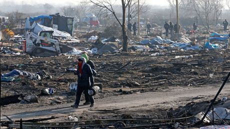 Migrants walk in the dismantled area of the camp for migrants called the