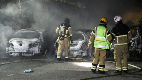 Firefighters extinguish a fire which had damaged cars after the vehicles had been set alight, in Malmo, Sweden © Johan Nilsson