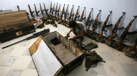 A rebel fighter of 'Al-Sultan Murad' brigade arranges weapons inside a warehouse in the northern Syrian rebel-controlled town of al-Rai, in Aleppo Governorate, Syria, September 26, 2016. © Khalil Ashawi