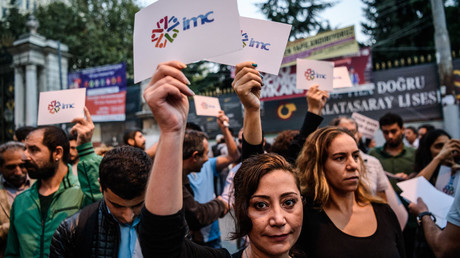 Employees and supporters of pro-Kurdish television channel IMC TV and supporters of other media previously closed by authorities hold signs bear the IMC logo during a demonstration in Istanbul on October 4, 2016 © Ozan Kose