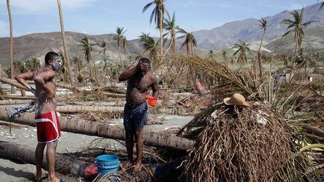 Men take a bath next to trees downed by Hurricane Matthew in Coteaux, Haiti, October 9, 2016. © Andres Martinez Casares