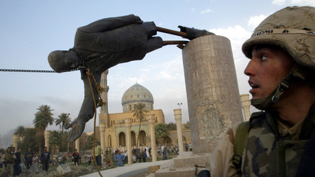 A U.S. soldier watches as a statue of Iraq's President Saddam Hussein falls in central Baghdad, Iraq April 9, 2003.© Goran Tomasevic