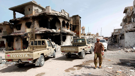 A fighter of Libyan forces allied with the U.N.-backed government walks past a ruined house in Cambo area which they captured from Islamic State militants on Sunday, in Sirte, Libya, October 17, 2016. © Ismail Zitouny