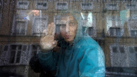 An Afghan adolescent migrant waves from a van as he departs with six others from the emergency shelter for minors in Saint Omer, France as they leave for Britain October 18, 2016. © Pascal Rossignol