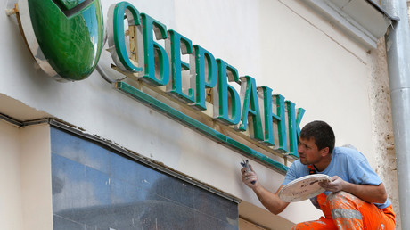 A worker paints the facade of a branch of Sberbank in central Moscow © Sergei Karpukhin