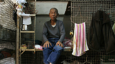 A resident takes a nap at one of about 100 cage homes in Hong Kong © Bobby Yip