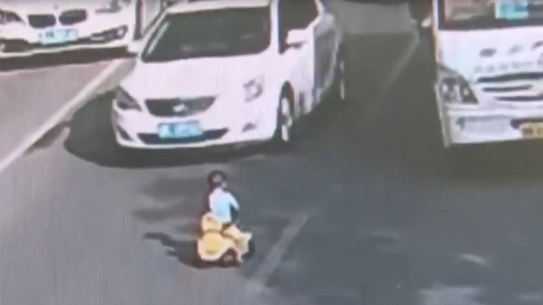 Toddler rides toy bike through rush hour traffic in China (VIDEO)