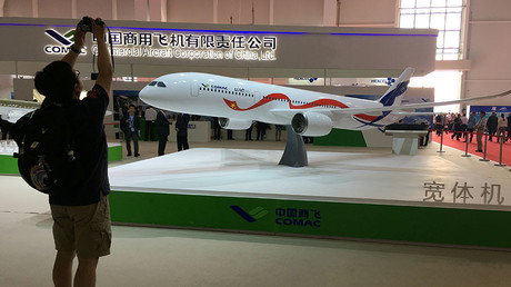 A man takes picture of the model of a widebody jet, which is planned to be developed by Commercial Aircraft Corporation of China and Russia's United Aircraft Corporation at an air show, the China International Aviation and Aerospace Exhibition, in Zhuhai, Guangdong Province, China, November 2, 2016.