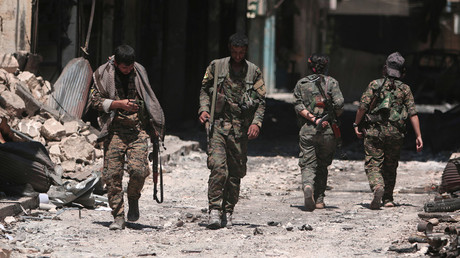 Syria Democratic Forces (SDF) fighters walk on the rubble of damaged shops and buildings in the city of Manbij, in Aleppo Governorate, Syria, August 10, 2016. © Rodi Said