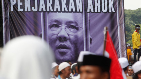 Members of hardline Muslim groups stand around a poster during protest against Jakarta's incumbent governor Basuki Tjahaja Purnama, an ethnic Chinese Christian running in the upcoming election, in Jakarta, Indonesia, November 4, 2016. Poster said