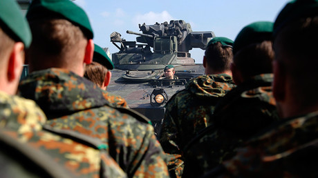 A Marder armoured infantry vehicle drives past German Bundeswehr armed forces soldiers © Fabrizio Bensch