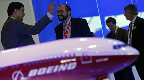 Visitors talk next to a Boeing 777X aircraft model at the Singapore Airshow © Edgar Su