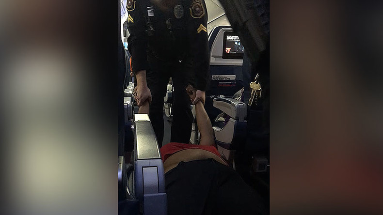 Woman dragged off flight by police for boarding plane too early (VIDEO)