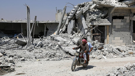 FILE PHOTO. A Syrian man rides his motorcycle past collapsed buildings in the northern Syrian town of Manbij. © Delil Souleiman