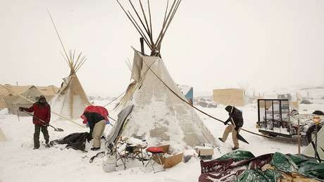 Campers maintain their tipi as high winds and a blizzard hit the Oceti Sakowin camp while