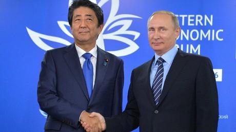 Russian President Vladimir Putin (R) shakes hands with Japanese Prime Minister Shinzo Abe © Aleksei Druzhinin