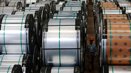 A worker walks past rolls of steel inside the China Steel Corporation factory, in Kaohsiung, southern Taiwan © Tyrone Siu