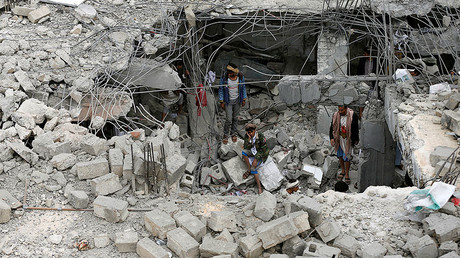 A man sits near others amidst rubble of a building destroyed by Saudi-led air strikes in the northwestern city of Amran, Yemen. File photo. © Khaled Abdullah