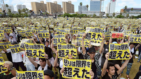 FILE PHOTO: Protesters raise placards reading