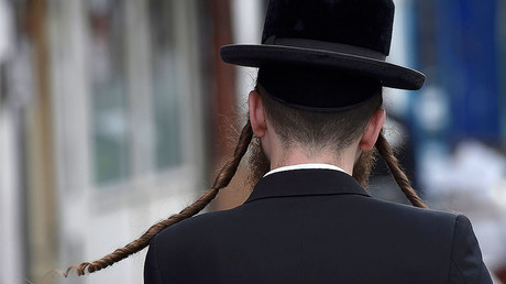 An orthodox Jewish man walks through a street in Stamford Hill north London, Britain. © Hannah McKay