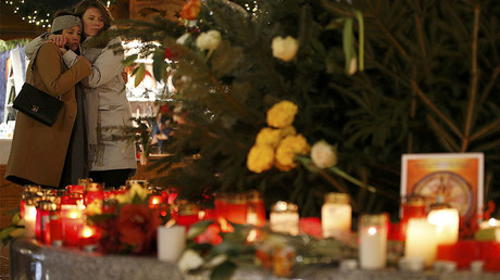 People mourn beside flowers and candles placed at the Christmas market at Breitscheid square in Berlin, Germany, December 22, 2016, following an attack by a truck which ploughed through a crowd at the market on Monday night. © Fabrizio Bensch