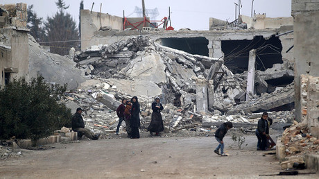 People stand near near rubble of damaged buildings in al-Rai town, northern Aleppo countryside, Syria December 25, 2016. © Khalil Ashawi